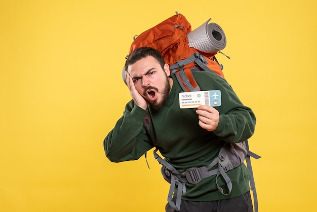 バックパックを持ち、黄色の背景にチケットを持っている感情的な神経質な旅行男の正面図