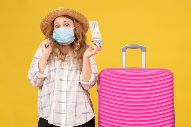 Вид спереди эмоциональной молодой леди в маске, показывающей билет и стоящей рядом со своей розовой сумкой