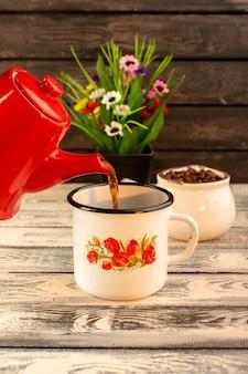 木製の机の上の赤いやかん茶色コーヒーの種子と花と空のカップの正面図