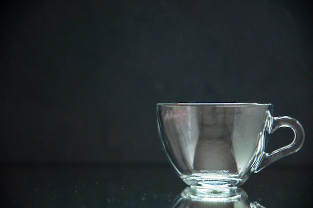 Вид спереди пустой стеклянной чашки с левой стороны на фоне темной волны со свободным пространством