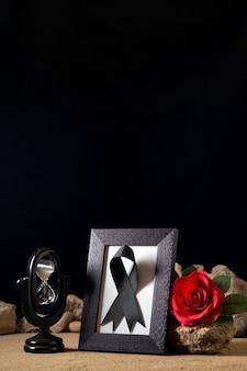 Вид спереди пустой фоторамки с красным цветком и камнями на черном