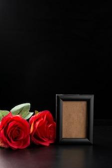 Вид спереди пустой фоторамки с красными розами на черном