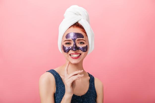 ピンクの背景で笑っているフェイスマスクを持つ魅惑的な女性の正面図。スパトリートメントをしている頭にタオルで至福の少女のスタジオショット。