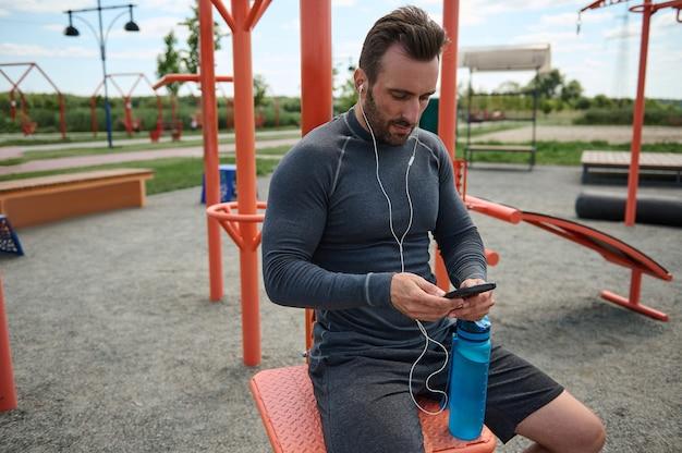 이어폰을 끼고 휴대폰을 들고 카피 공간이 있는 검은색 빈 화면에 손가락을 대고 있는 유럽 스포츠맨의 전면 전망. 심장 박동을 확인하는 모바일 애플리케이션에서 운동하는 선수