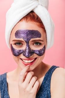 スパトリートメント中に楽しんで興奮している女の子の正面図。ピンクの背景に笑みを浮かべてフェイスマスクと幸せなヨーロッパの女性のスタジオショット。