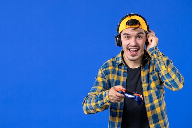 青い壁でビデオゲームをプレイしているオレンジ色のゲームパッドを持つ興奮した男性ゲーマーの正面図