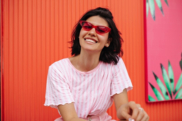 스트라이프 티셔츠에 흥분된 여자의 전면 모습. 핑크 선글라스에 무두 질된 여자 웃음의 야외 샷.