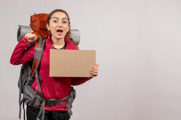 灰色の壁に段ボールを保持している大きなバックパックと興奮した若い旅行者の正面図