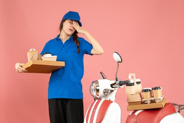 パステル ピーチ色の背景にコーヒーと小さなケーキを保持しているオートバイの隣に立っている疲れ切った宅配便の女の子の正面図