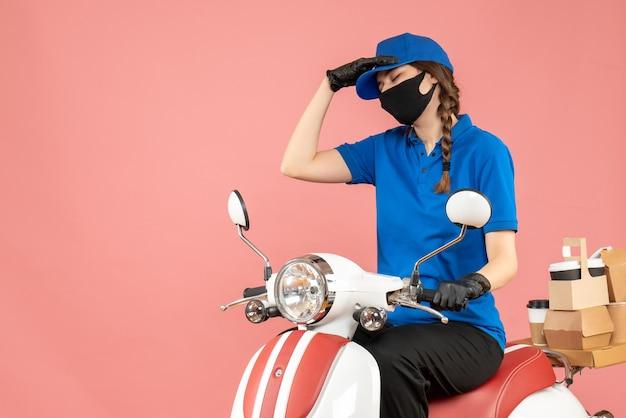 파스텔 복숭아 배경에 주문을 전달하는 스쿠터에 앉아 의료 마스크와 장갑을 끼고 지친 택배 소녀의 전면보기