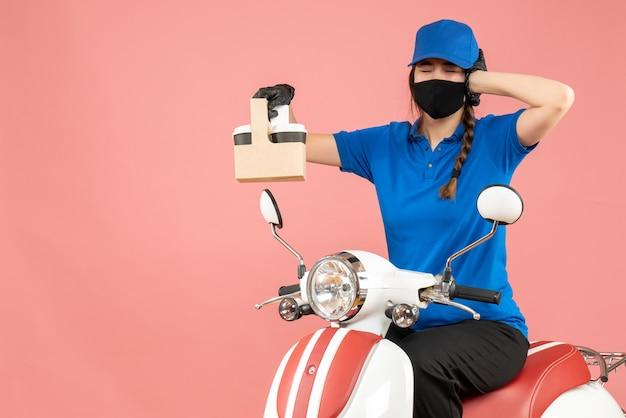 パステル調の桃の背景に注文を保持しているスクーターに座っている医療用マスクと手袋をはめた疲れ果てた女性配達員の正面図