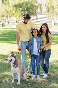 Семья с мальчиком и собакой в парке, вид спереди