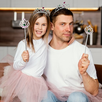 Вид спереди отца и дочери, играющих с тиарой и палочкой