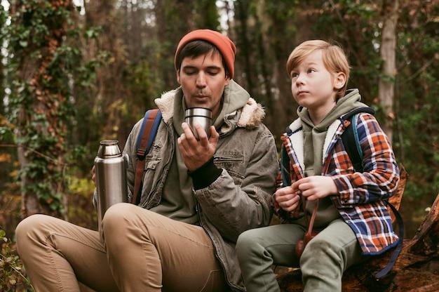 自然の中で屋外で熱いお茶を飲んでいる父と息子の正面図
