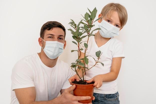 植物のポットを保持している父と息子の正面図