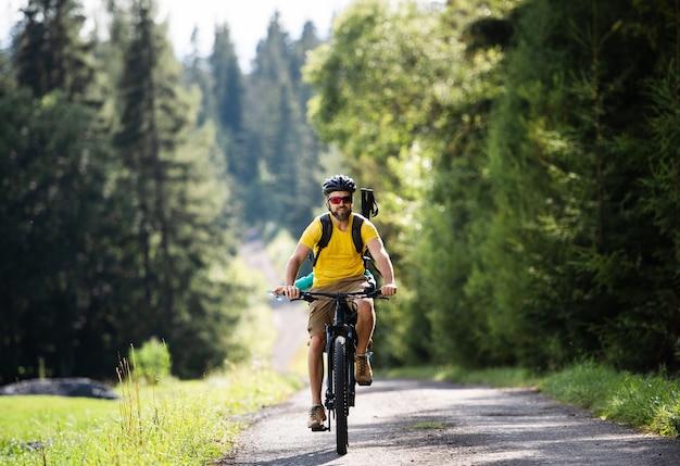 夏の自然の中で屋外でサイクリングする小さな子供を持つ父親、スロバキアのハイタトラの正面図。