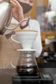 Вид спереди женского бариста, процеживающего кофе