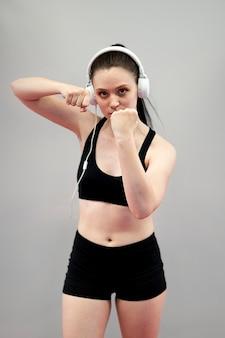 練習のヘッドフォンで女性ボクサーの正面図