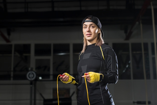 보호 장갑 및 점프 로프와 함께 여성 복서의 전면보기