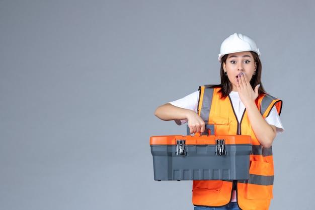 흰 벽에 무거운 도구 케이스를 들고 있는 여성 건축업자의 전면 모습
