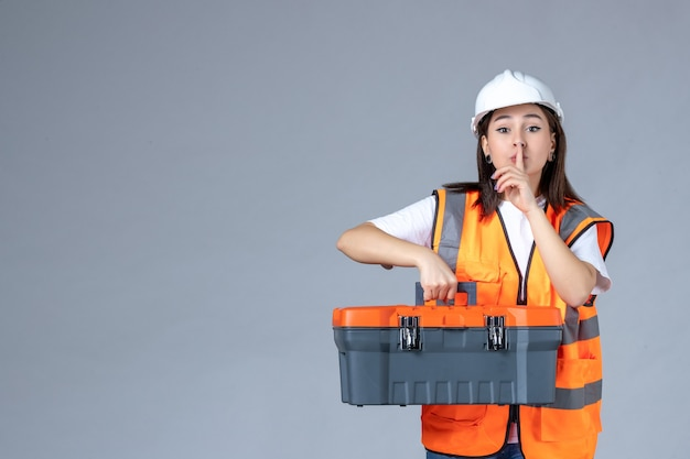 白い壁に重いツールケースを運ぶ女性ビルダーの正面図