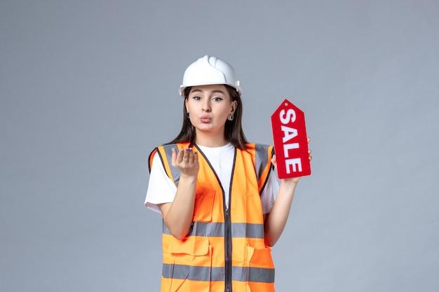 灰色の壁に赤い販売ボードを保持している女性ビルダーの正面図