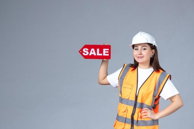 회색 벽에 빨간색 판매 보드를 들고 있는 여성 건축업자의 전면 모습