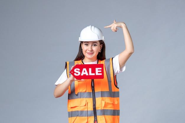 흰 벽에 빨간색 판매 보드를 들고 있는 여성 건축업자의 전면 모습