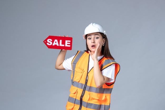 白い壁に赤い販売ボードを保持している女性ビルダーの正面図