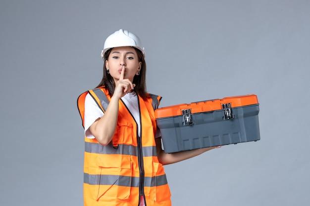 도구 케이스를 들고 회색 벽에 침묵을 요구하는 여성 건축업자의 전면 모습