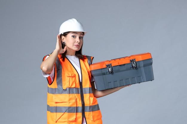 灰色の壁にツールケースを保持している女性ビルダーの正面図