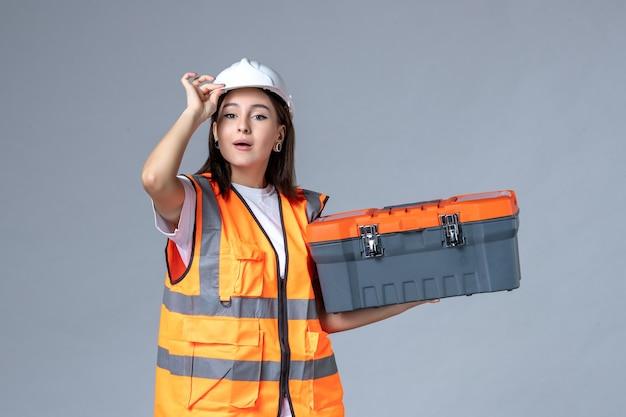 회색 벽에 도구 케이스를 들고 있는 여성 건축업자의 전면 모습