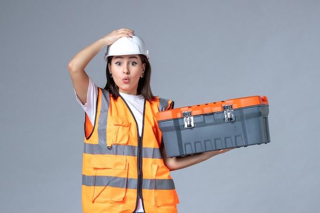 Вид спереди женщины-строителя, держащей чемодан для инструментов на серой стене