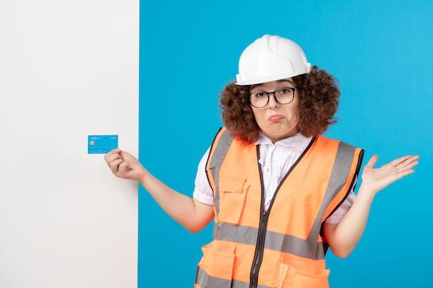 파란색 벽에 유니폼과 헬멧에 여성 작성기의 전면보기