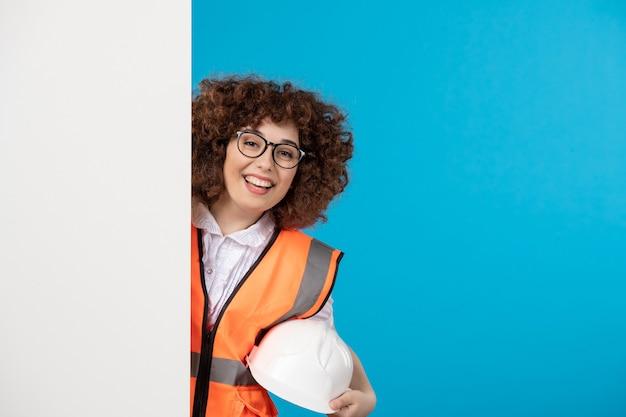 파란색 벽에 제복을 입은 여성 빌더의 전면보기