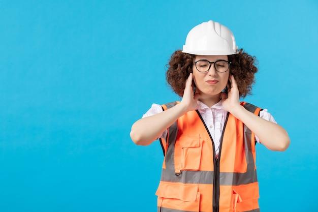 青い壁に頭痛を持っている制服を着た女性ビルダーの正面図