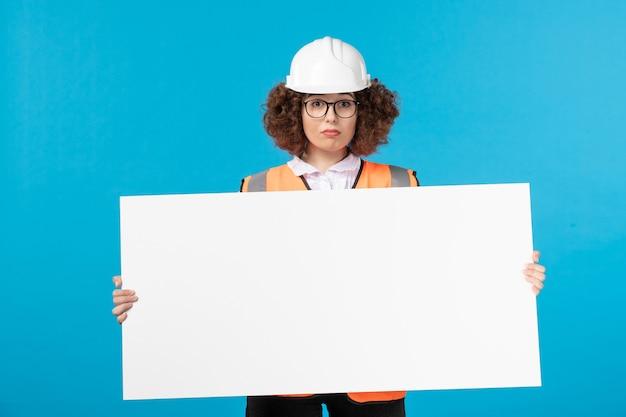 青い壁に無地の机を保持している制服を着た女性ビルダーの正面図