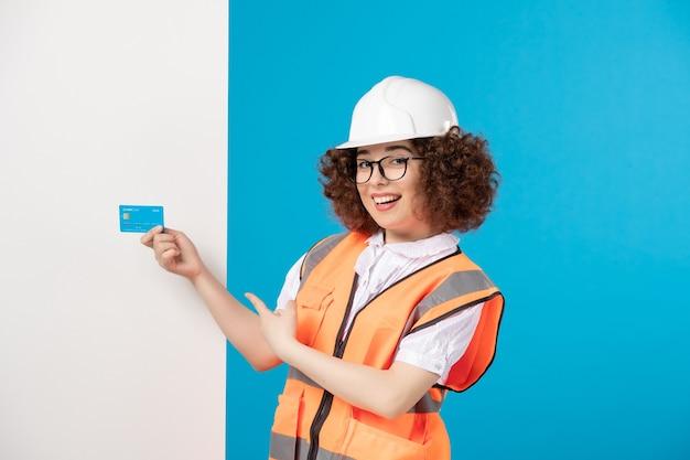 青い壁に制服を着た女性ビルダーの正面図