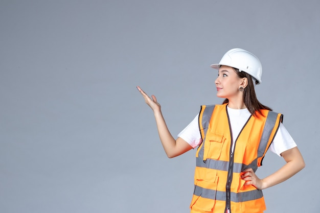 회색 벽에 제복을 입은 여성 건축업자의 전면 모습