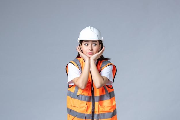 灰色の壁に制服を着た女性ビルダーの正面図
