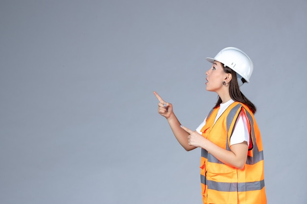 白い壁に制服を着た女性ビルダーの正面図
