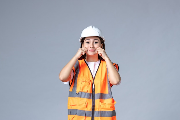 흰 벽에 제복을 입은 여성 건축업자의 전면 모습