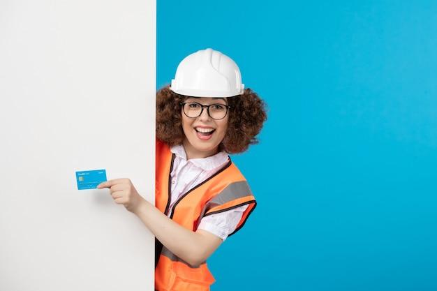 파란색 벽에 파란색 은행 카드와 제복을 입은 여성 빌더의 전면보기