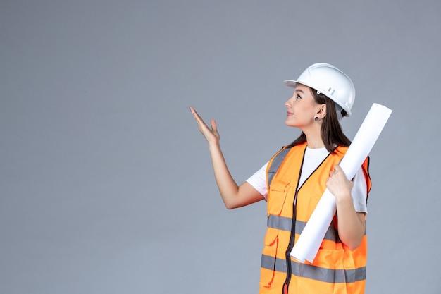 회색 벽에 손에 포스터가 있는 제복을 입은 여성 건축업자의 전면