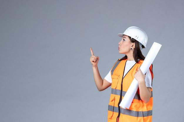 灰色の壁に彼女の手でポスターと制服を着た女性ビルダーの正面図