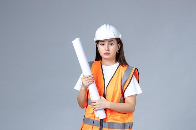 흰색 벽에 손에 포스터가 있는 제복을 입은 여성 건축업자의 전면 모습