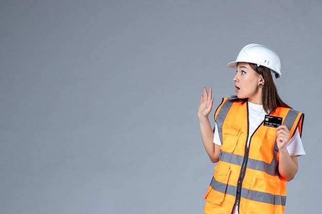 灰色の壁に彼女の手で黒い銀行カードを持つ女性ビルダーの正面図