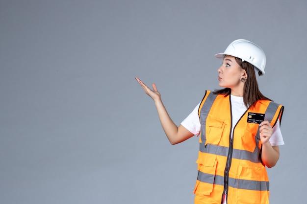 회색 벽에 손에 검은색 은행 카드를 들고 있는 여성 건축업자의 전면 모습