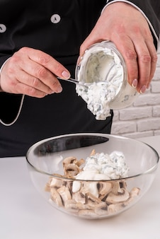 Вид спереди шеф-повара женского пола, добавляющего соус к грибам