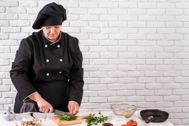 Вид спереди шеф-повар женщина измельчения зелени